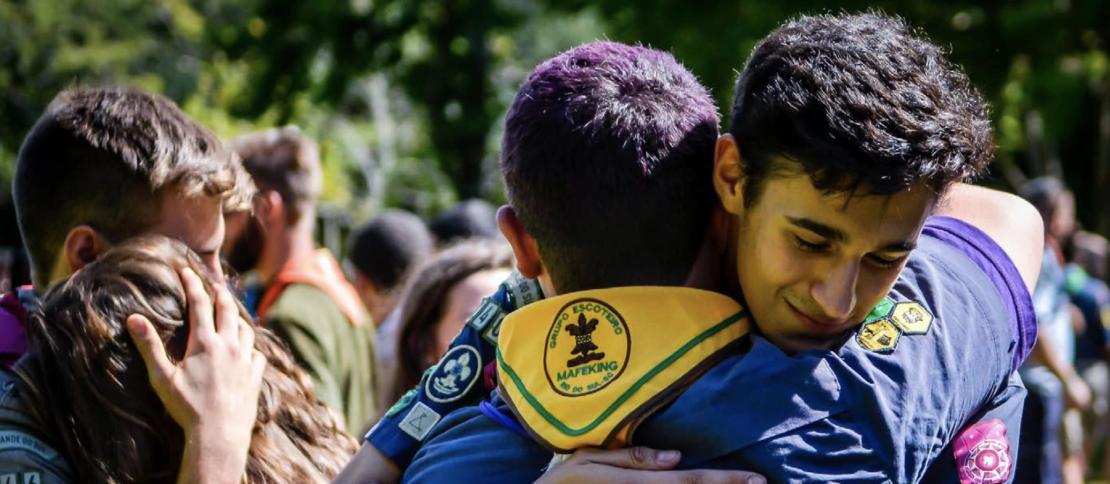 Dois jovens escoteiros se abraçando